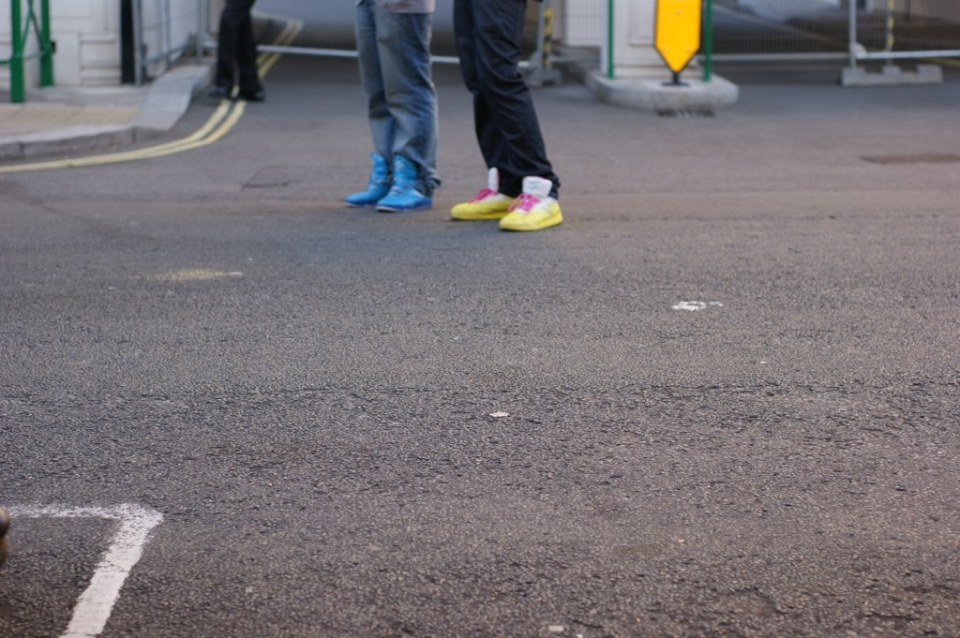 photo looking across the street at two people wearing jeans, each wearing a colourful set of trainers, on bright blue, ther other pair neon yellow. The photo focus is on the tarmac a meter or two in front of the people. The photo only includes their shoes and jeans up to their knees.