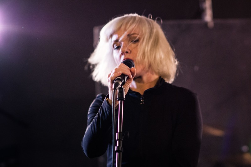 Jane Horrocks singing into a mic, with her white blonde hair swinging as she performs