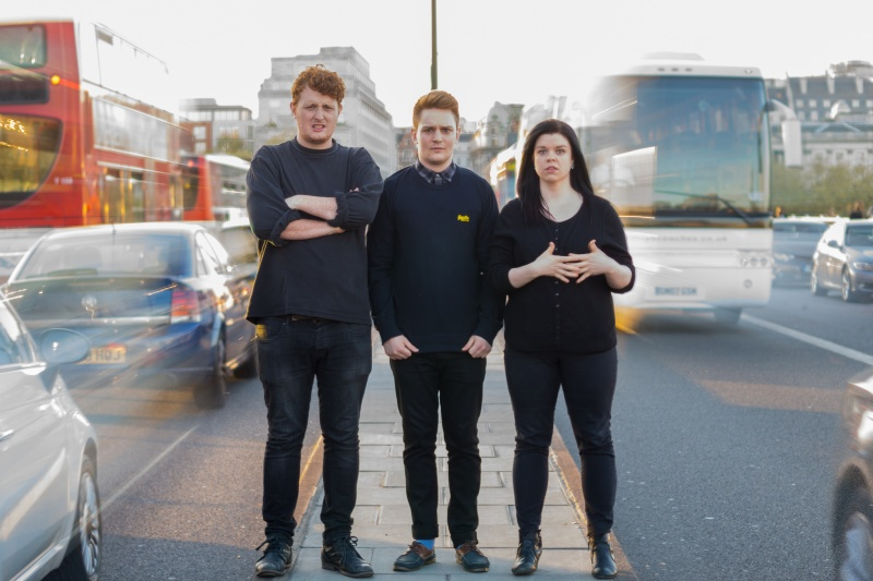 Comedy trio Minor Delays promo shoot standing between busy traffic on Waterloo Bridge