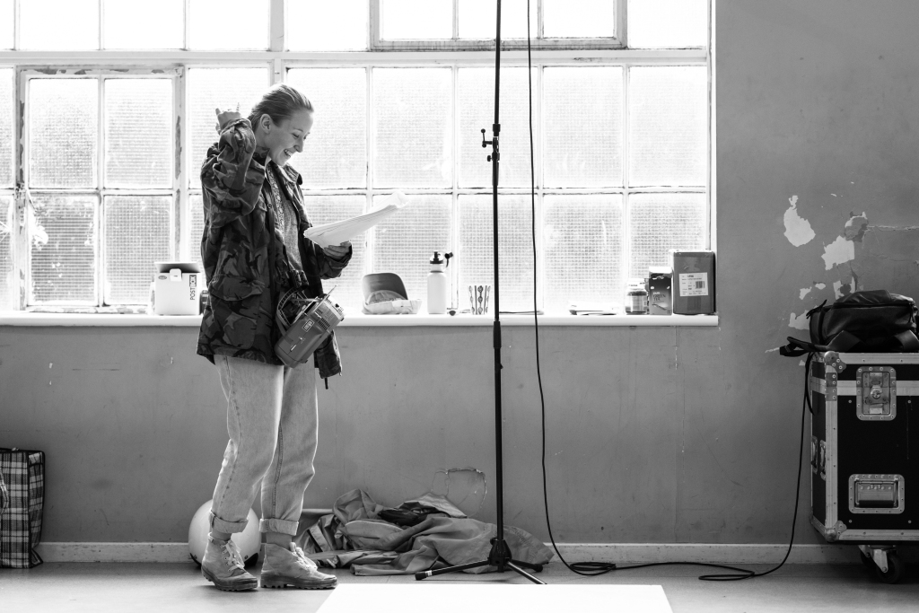 Erin Doherty smiles as she reads her script in front of a bright window. She's wearing a camo jacket, loose jeans and ankle boots.